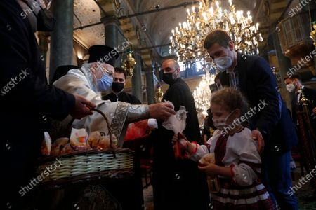 Stock Image of Ecumenical Patriarch Bartholomew I, left, the spiritual leader of the world's Orthodox Christians, hands out presents to Ukrainian faithful following the Easter service with limited attendance as part of the measures to contain the spread of the coronavirus, at the Patriarchal Cathedral of St. George in Istanbul, . For Orthodox Christians, this is normally a time of reflection and joy, of centuries-old ceremonies steeped in symbolism and tradition.But for a second year, Easter, by far the most significant religious holiday for the world's roughly 300 million Orthodox, has essentially been toned down in a world still struck by the COVID-19 pandemic
