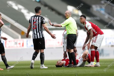 Newcastle's Fabian Schaer, left, reacts after he performed a challenge on Arsenal's Gabriel Martinelli, laying down, for which he was given a straight red card from referee Mike Dean during the English Premier League soccer match between Newcastle United and Arsenal at St James' Park stadium, in Newcastle, England