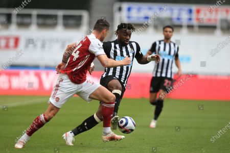 Newcastle's Allan Saint-Maximin competes for the ball with Arsenal's Granit Xhaka, left, during the English Premier League soccer match between Newcastle United and Arsenal at St James' Park stadium, in Newcastle, England
