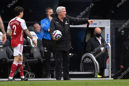 Stock Image of Newcastle's head coach Steve Bruce holds the ball during the English Premier League soccer match between Newcastle United and Arsenal at St James' Park stadium, in Newcastle, England