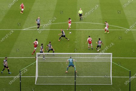 Arsenal's Mohamed Elneny, center top, scores his side's first goal during the English Premier League soccer match between Newcastle United and Arsenal at St James' Park stadium, in Newcastle, England