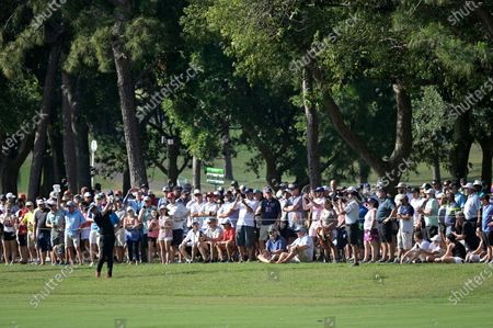 Spectators watch as Keegan Bradley hits from the 16th fairway during the final round of the Valspar Championship golf tournament, in Palm Harbor, Fla