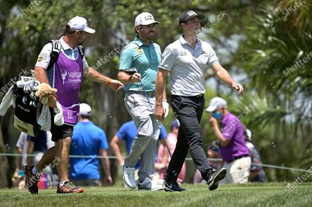 Viktor Hovland, right, of Norway, and Louis Oosthuizen, center, of South Africa, walk on the fifth fairway after hitting their tee shots during the final round of the Valspar Championship golf tournament, in Palm Harbor, Fla
