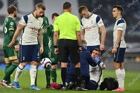 Tottenham's Giovani Lo Celso, second right, is injured during the English Premier League soccer match between Tottenham and Sheffield United, at the Tottenham Hotspur Stadium in London