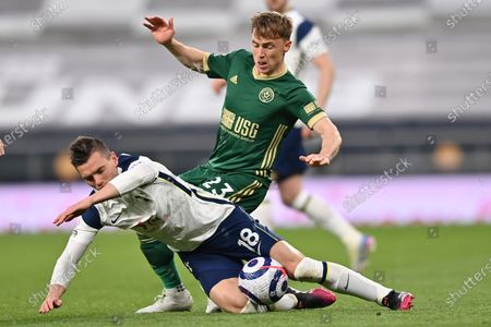 Stock Picture of Tottenham's Giovani Lo Celso is challenged by Sheffield United's Ben Osborn, rear, during the English Premier League soccer match between Tottenham and Sheffield United, at the Tottenham Hotspur Stadium in London