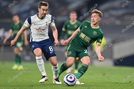 Tottenham's Harry Winks, left, is challenged by Sheffield United's Ben Osborn during the English Premier League soccer match between Tottenham and Sheffield United, at the Tottenham Hotspur Stadium in London