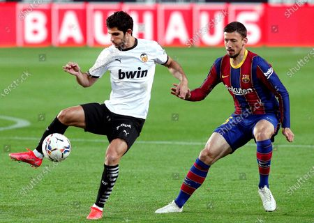 Valencia's Goncalo Guedes (L) in action against FC Barcelona's Charles Lenglet (R) during the Spanish La Liga soccer match between Valencia CF and FC Barcelona at Mestalla stadium in Valencia, eastern Spain, 02 May 2021.