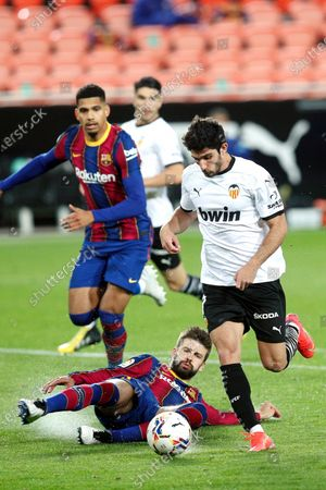 Valencia's Goncalo Guedes (R) in action against FC Barcelona's Gerard Pique (bottom) during the Spanish La Liga soccer match between Valencia CF and FC Barcelona at Mestalla stadium in Valencia, eastern Spain, 02 May 2021.