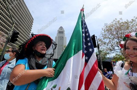 . Los Angeles residents Marta Samano, left, and Eva Romero Ruelas unfurl American and Mexican flags during a May Day march and rally in downtown Los Angeles on Saturday, May 1, 2021. (Luis Sinco / Los Angeles Times)