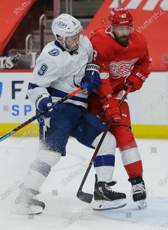 Tampa Bay Lightning center Tyler Johnson (9) checks into Detroit Red Wings defenseman Filip Hronek (17) during the first period of an NHL hockey game, in Detroit