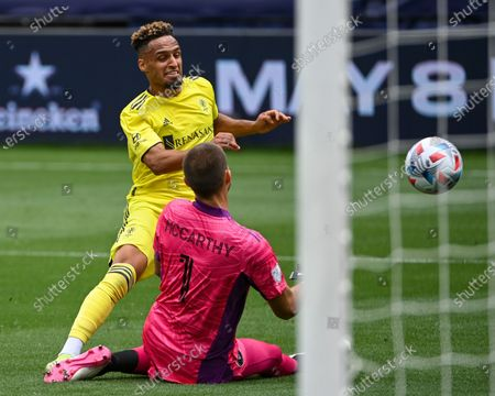 Nashville midfielder, Hany Mukhtar (10), takes a shot on goal that is deflected by Inter Miami goalkeeper, John McCarthy (1), during the MLS match between Inter Miami and Nashville SC at Nissan Stadium in Nashville, TN