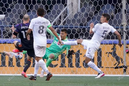 Seattle Sounders defender Brad Smith (11) kicks a goal past Los Angeles Galaxy goalkeeper Jonathan Bond, right, during the first half of an MLS soccer match, in Seattle, as Galaxy's Jonathan dos Santos (8) and Daniel Steres (5) defend