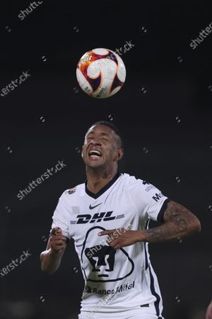 Stock Image of Pumas Gabriel Torres goes for the ball during a Mexican soccer league match against America at University Olympic Stadium in Mexico City