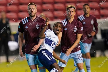 Vancouver Whitecaps forward Deiber Caicedo, center, reacts after shooting on goal as Colorado Rapids' Danny Wilson, left, and Cole Bassett (26) defend in the second half of an MLS soccer game, in Sandy, Utah