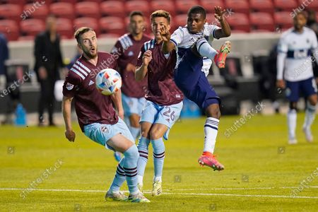 Vancouver Whitecaps forward Deiber Caicedo, center, shoots as Colorado Rapids' Danny Wilson, left, and Cole Bassett (26) defend in the second half of an MLS soccer game, in Sandy, Utah