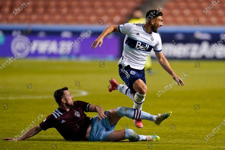 Colorado Rapids defender Danny Wilson, left, and Vancouver Whitecaps forward Lucas Cavallini battle for the ball in the second half of an MLS soccer game, in Sandy, Utah