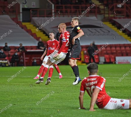 Stock Picture of Watson of Charlton watches as Tom Hopper scores for 3-1 in minute 88; The Valley, London, England; English Football League One Football, Charlton Athletic versus Lincoln City.