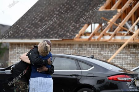 Neighbors Alfred Lee and Grace Bazzy hug in front of another neighbor's damaged home along Elvis Presley Drive in Tupelo, Miss., . Multiple tornadoes were reported across Mississippi on Sunday, causing some damage but no immediate word of injuries