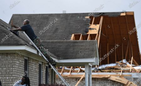 Alfred Lee covers a damaged spot on the roof of his home on Elvis Presley Drive in Tupelo, Miss., . Multiple tornadoes were reported across Mississippi on Sunday, causing some damage but no immediate word of injuries