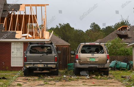 """Damaged homes and vehicles are seen along Elvis Presley Drive in Tupelo, Miss., . A line of severe storms rolled through the state Sunday afternoon and into the nighttime hours. Late Sunday, a """"tornado emergency"""" was declared for Tupelo and surrounding areas"""