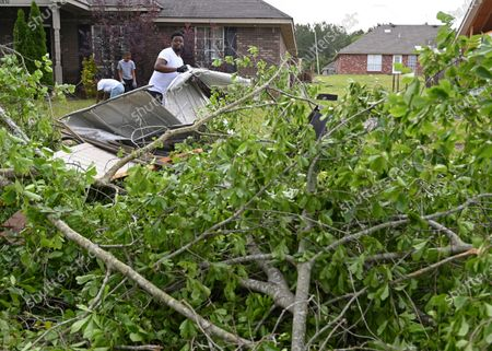 Stock Picture of Derrick Pounds clears debris from around his house on Elvis Presley Drive in Tupelo, Miss., . Multiple tornadoes were reported across the state on Sunday
