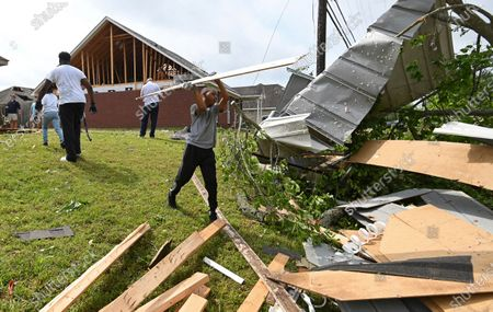 Derrick Pounds Jr. helps his father clean up debris around their house on Elvis Presley Drive in Tupelo, Miss., . Multiple tornadoes were reported across the state on Sunday