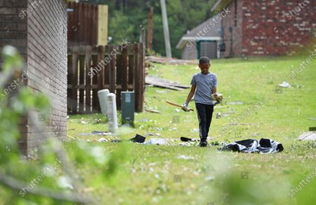 Derrick Pounds Jr., 7, picks up debris around his house on Elvis Presley Drive in Tupelo, Miss., . Multiple tornadoes were reported across the state on Sunday