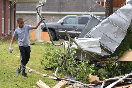 Stock Photo of Derrick Pounds Jr., 7, helps clear debris around his house on Elvis Presley Drive in Tupelo, Miss., . Multiple tornadoes were reported across the state on Sunday