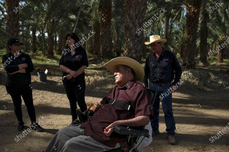 Enrique Bautista, 70, paralyzed in a traffic accident in 2004, with three children Maricela Bautista, left, Alicia Gonzalez, and Alvaro Bautista at Family Organic Date Farm on Thursday, April 8, 2021 in Mecca, CA.(Irfan Khan / Los Angeles Times)