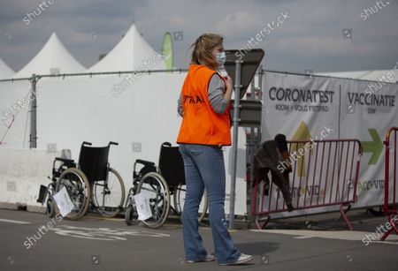 Steward stands in front of wheelchairs as she waits to guide people who will receive their COVID-19 vaccination at the Vaccine Village in Antwerp, Belgium, . The Vaccine Village in Antwerp on Monday passed a milestone of 100,000 COVID-19 vaccinations recorded since the center opened. In the coming weeks they hope to expand their capacity even further