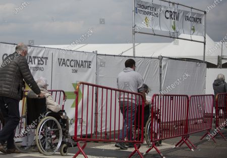 People wait in a line to receive their COVID-19 vaccine at the Vaccine Village in Antwerp, Belgium, . The Vaccine Village in Antwerp on Monday passed a milestone of 100,000 vaccinations recorded since the center opened. In the coming weeks they hope to expand their capacity even further