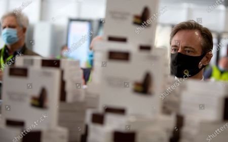 Mayor of Antwerp, Bart De Wever, sits with volunteers behind boxes of chocolates to give out to staff during an event at the Vaccine Village in Antwerp, Belgium, . The Vaccine Village in Antwerp on Monday passed a milestone of 100,000 COVID-19 vaccinations recorded since the center opened. In the coming weeks they hope to expand their capacity even further