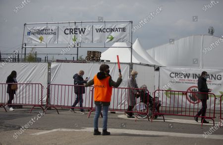 Steward guides people where to wait in a line to receive their COVID-19 vaccine at the Vaccine Village in Antwerp, Belgium, . The Vaccine Village in Antwerp on Monday passed a milestone of 100,000 vaccinations recorded since the center opened. In the coming weeks they hope to expand their capacity even further