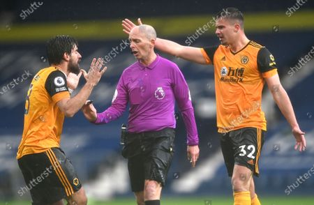 Wolverhampton Wanderers' Ruben Neves, left, and Leander Dendoncker complain to referee Mike Dean during an English Premier League soccer match between West Bromwich Albion and Wolverhampton Wanderers at The Hawthorns in West Bromwich, England
