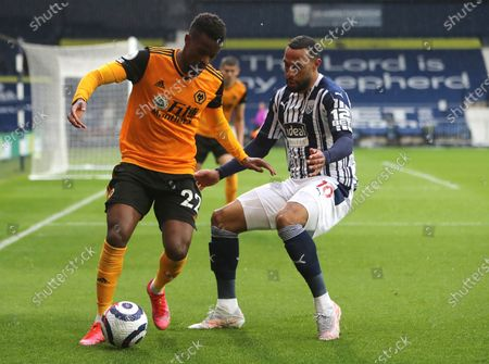 Wolverhampton Wanderers' Nelson Semedo, left, and West Bromwich Albion's Matt Phillips challenge for the ball during an English Premier League soccer match between West Bromwich Albion and Wolverhampton Wanderers at The Hawthorns in West Bromwich, England
