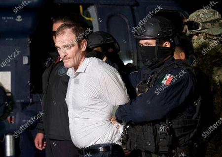 """Provided by the Mexican Attorney General's Office, Hector """"El Guero"""" Palma, or """"Blondie,"""" one of the founders of the Sinaloa Cartel, is escorted in handcuffs from a helicopter at a federal hangar in Mexico City, after serving almost a decade in a U.S. prison and transported to another maximum-security lockup to await trial for two murders"""