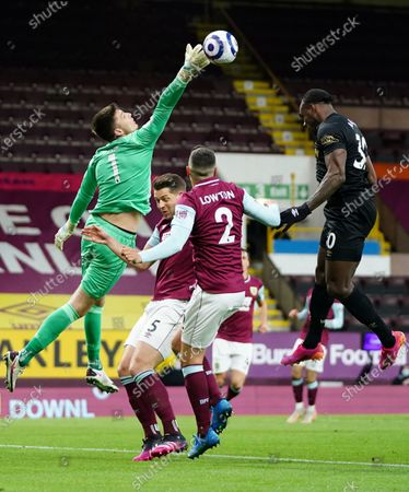 Burnley's goalkeeper Nick Pope tips the ball away from West Ham's Michail Antonio, right during the English Premier League soccer match between Burnley and West Ham United and at Turf Moor stadium in Burnley, England