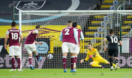 Burnley's Chris Wood, second left, shoots and scores the opening goal from the penalty spot past West Ham's goalkeeper Lukasz Fabianski during the English Premier League soccer match between Burnley and West Ham United and at Turf Moor stadium in Burnley, England