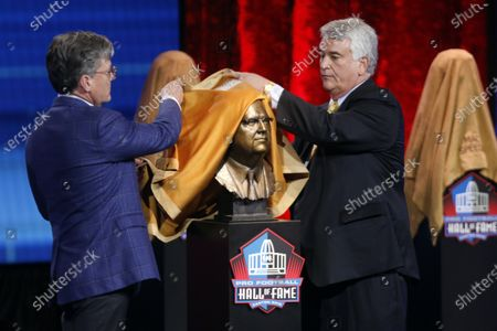 Tim Connor, left, and Michael Connor unveil the bust of their uncle George Young at the Pro Football Hall of Fame Enshrinement ceremony in Canton, Ohio