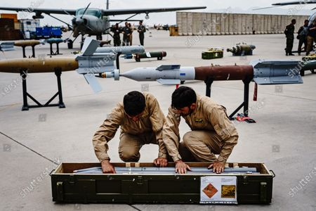 Stock Image of Members of the 777 Special Mission Wing load ordinances into a container during a visit by Chief of General Staff of the Armed Forces Gen. Mohammad Yasin Zia, at their base in Kabul, Afghanistan, Wednesday, April 28, 2021. (MARCUS YAM / LOS ANGELES TIMES)