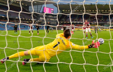 Burnley's Chris Wood (back R) scores the 1-0 lead from the penalty spot against West Ham's goalkeeper Lukasz Fabianski (front) during the English Premier League soccer match between Burnley FC and West Ham United in Burnley, Britain, 03 May 2021.