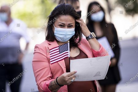 Patricia Guadalupe Rivas Lopez from El Salvador reacts holding her naturalization certificate during a US naturalization ceremony outdoor in the courtyard behind a federal building in Downtown Los Angeles, California, USA, 03 May 2021. 25 new US citizens hail from the following 15 countries: Algeria, Armenia, Brazil, China, Colombia, Egypt, El Salvador, Iran, Israel, Mexico, Philippines, South Korea, Switzerland, Thailand and Venezuela swore allegiance and became US citizens.