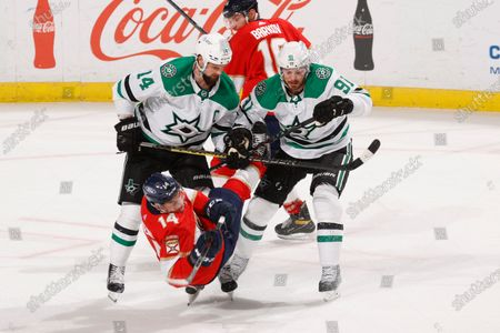 Stock Image of Dallas Stars center Tyler Seguin (91) and left-wing Jamie Benn (14) check Florida Panthers left wing Grigori Denisenko (14) during the third period of an NHL hockey game, in Sunrise, Fla
