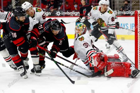 Carolina Hurricanes' Nino Niederreiter (21) and Vincent Trocheck (16) battle with Chicago Blackhawks' Ian Mitchell (51) and goaltender Collin Delia (60) with Blackhawks' Pius Suter (24) looking on during the second period of an NHL hockey game in Raleigh, N.C