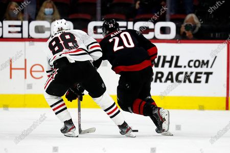 Carolina Hurricanes Sebastian Aho (20) skates with the puck with Chicago Blackhawks' Patrick Kane (88) close behind during the third period of an NHL hockey game in Raleigh, N.C