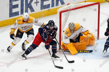 Nashville Predators' Alexandre Carrier, left, tries to stop Columbus Blue Jackets' Cam Atkinson, center, from taking a shot against Nashville Predators' Juuse Saros during the first period of an NHL hockey game, in Columbus, Ohio