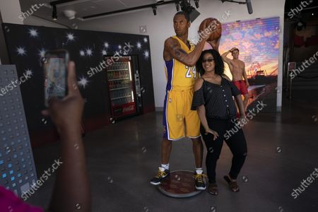 Priacia Chery, a registered nurse visiting from Florida, poses for photos with a wax figure of late NBA star Kobe Bryant at Madame Tussauds Hollywood in the Hollywood section of Los Angeles, . Los Angeles County is expected to move into the least-restrictive yellow tier this week, amid the coronavirus pandemic