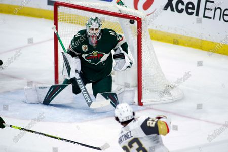 Vegas Golden Knights defenseman Alec Martinez (23) scores a goal against Minnesota Wild goaltender Cam Talbot, top, in the first period during an NHL hockey game, in St. Paul, Minn