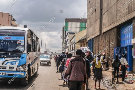 Nairobi residents walk past the busy traffic after the government lifted the inter-county Cessation of movement in and out of Nairobi. Addressing the Nation from State house in his full Labour Day speech, President Uhuru Kenyatta on May 1st, lifted a curb on all public transports and cross-county travels as Schools and learning institutions prepare to reopen on May 10th as per the Ministry of Education Academic Calendar. The president also extended the nation wide curfew across Nairobi, Machakos, Kajiado, Kiambu and Nakuru back to 10 pm to 4am daily for a period of 30 days.