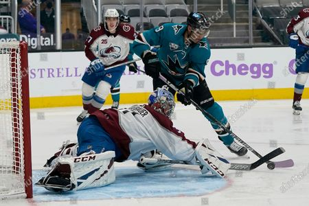 Colorado Avalanche goaltender Philipp Grubauer, bottom, defends a shot by San Jose Sharks left wing Evander Kane (9) during the third period of an NHL hockey game in San Jose, Calif